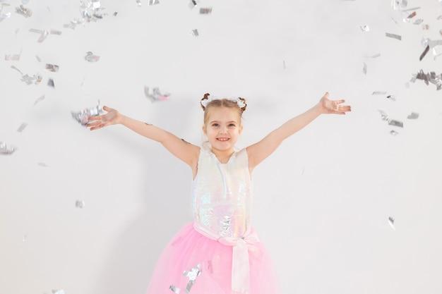 Koncepcja strony, święta, urodziny, nowy rok i uroczystości - słodkie dziecko rzuca konfetti.