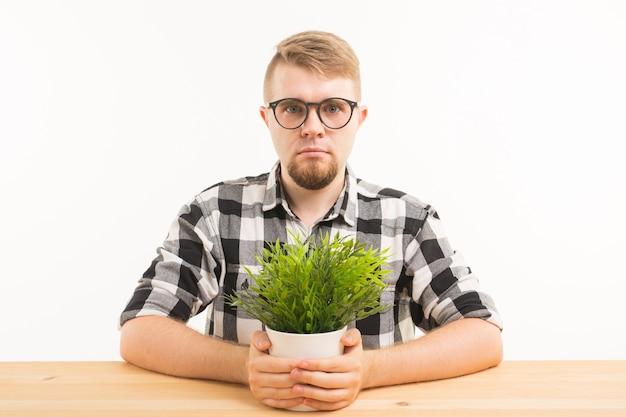 Koncepcja studenta, biura i ludzi - młody zrzędliwy mężczyzna siedzi przy stole z zieloną rośliną