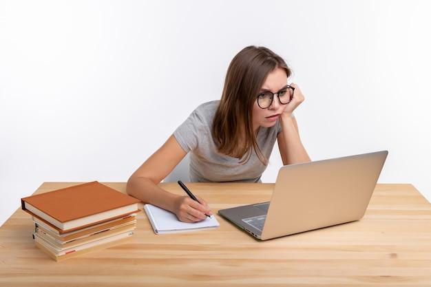 Koncepcja studentów i edukacji. przemyślana młoda kobieta siedzi przy drewnianym stole z laptopem