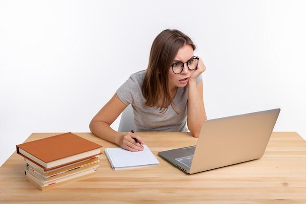 Koncepcja studentów i edukacji - przemyślana młoda kobieta siedzi przy drewnianym stole z laptopem