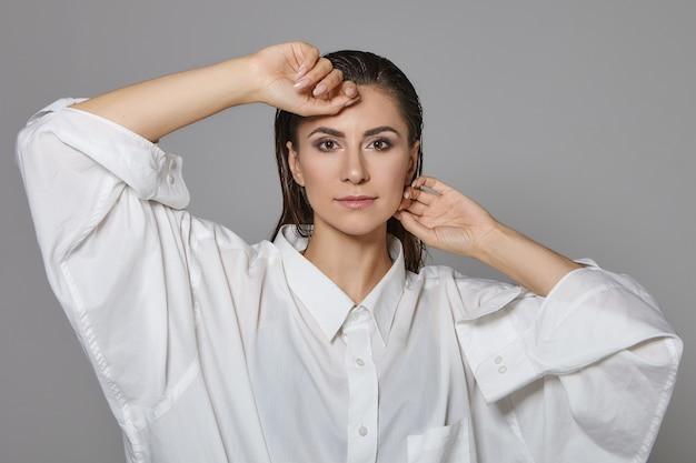Koncepcja stylu i mody. obraz pięknej efektownej brunetki modelki z zadymionymi oczami makijaż i ciemnymi włosami zaczesanymi do tyłu, pozowanie na białym tle w obszernej białej koszuli, ręce na twarzy