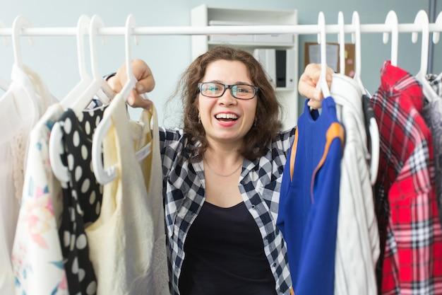 Koncepcja stylu, mody i ludzi - piękna młoda kobieta wybiera sukienki