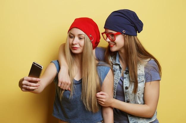 Koncepcja stylu życia, emocji, technologii i ludzi: dwie młode dziewczyny hipster przyjaciółki biorąc selfie na żółto