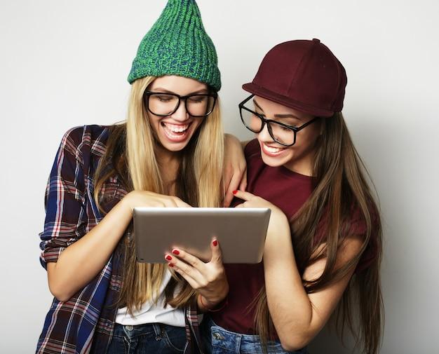 Koncepcja stylu życia i ludzi: dwie hipsterskie przyjaciółki używają cyfrowego tabletu