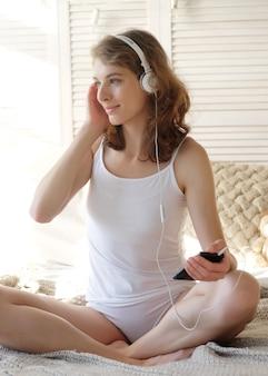 Koncepcja stylu życia i ludzi: piękna zadowolona dziewczyna w piżamie słuchająca muzyki za pomocą słuchawek i tańcząca na białym łóżku
