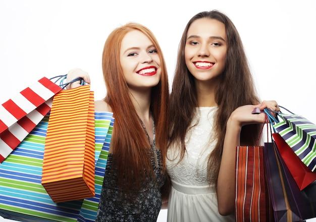 Koncepcja stylu życia i ludzi: portret dwóch pięknych młodych kobiet z torbami na zakupy