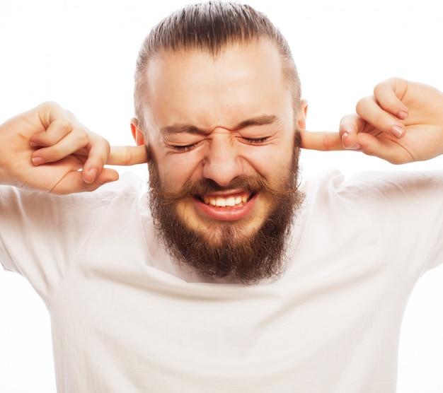 Koncepcja stylu życia i ludzi: sfrustrowany brodaty mężczyzna w białej koszuli trzymający palce w uszach i trzymający oczy zamknięte, stojąc na tle białej przestrzeni