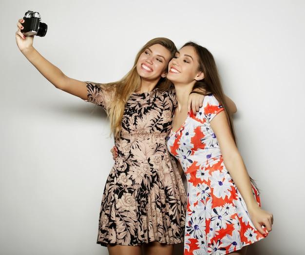 Koncepcja stylu życia i ludzi: szczęśliwe dziewczyny robiące zdjęcia na szarym tle