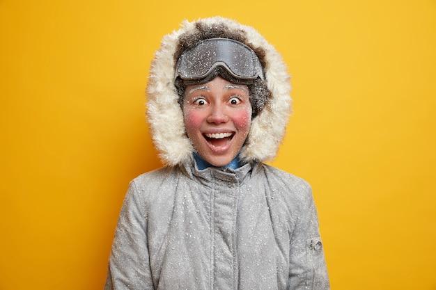 Koncepcja stylu życia i zimowych zajęć ludzi. wesoła ciemnoskóra kobieta uśmiecha się szeroko, pełna szczęścia, nosi kurtkę zimową i gogle narciarskie.