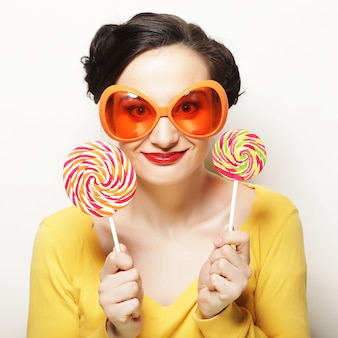 Koncepcja stylu życia, ludzi i partii: zabawna kobieta w dużych pomarańczowych okularach z dużym lizakiem. przyjęcie urodzinowe.
