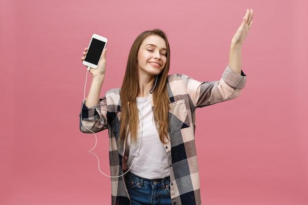 Koncepcja stylu życia. młoda kobieta przy użyciu telefonu do słuchania muzyki