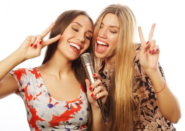 Koncepcja stylu życia, szczęścia, emocji i ludzi: dwie młode dziewczyny śpiewają na białym tle
