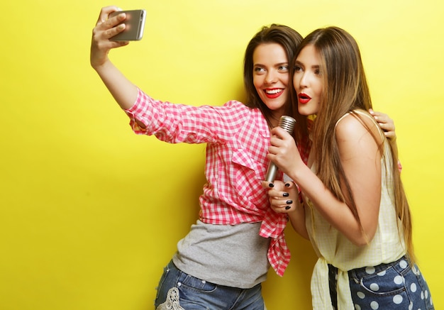 Koncepcja stylu życia, szczęścia, emocji i ludzi: dwie piękne hipsterki z mikrofonem robią selfie na żółtym tle