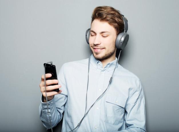Koncepcja stylu życia, szczęścia, emocji i ludzi: mężczyzna trzymający telefon komórkowy i licytujący muzykę na szarej przestrzeni