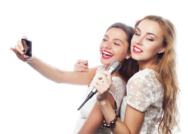 Koncepcja stylu życia, szczęścia, emocji i ludzi: piękne dziewczyny z mikrofonem śpiewają i robią selfie