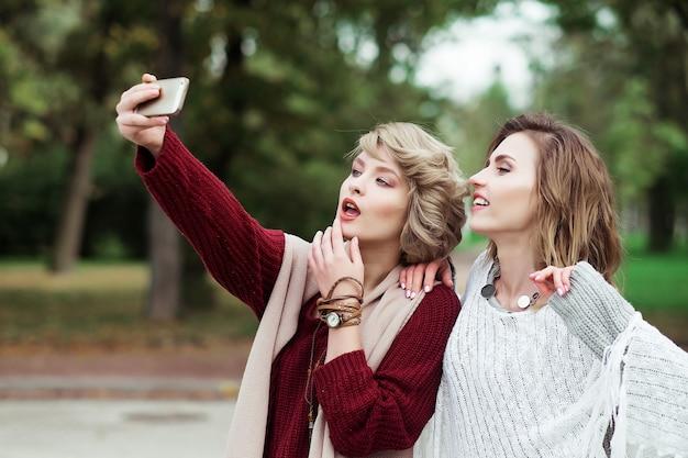 Koncepcja stylu życia, szczęścia, emocji i ludzi: przyjaciele co selfie. dwie piękne młode kobiety co selfie w jesiennym parku.