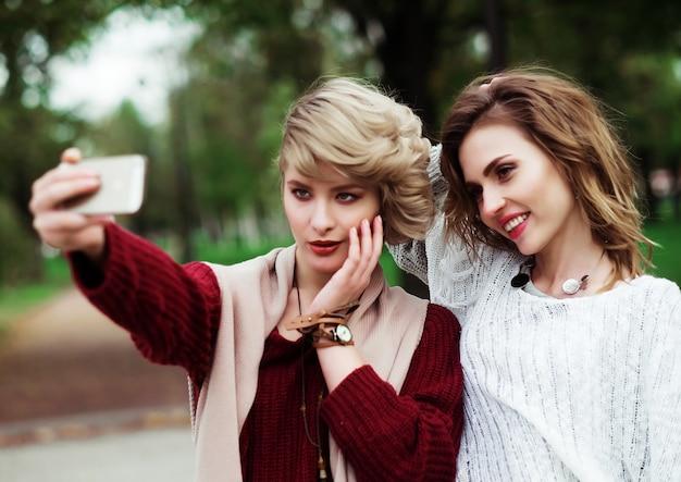 Koncepcja stylu życia, szczęścia, emocji i ludzi: przyjaciele robiąc selfie. dwie piękne młode kobiety co selfie w parku jesień.