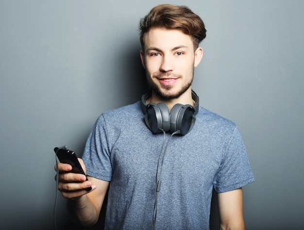 Koncepcja stylu życia, szczęścia, emocji i ludzi: przystojny młody mężczyzna ze słuchawkami na szyi, trzymając telefon komórkowy i uśmiechnięty, stojąc przed szarej przestrzeni