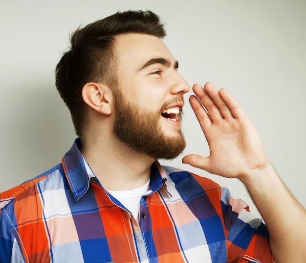 Koncepcja stylu życia, szczęścia i ludzi: młody brodaty mężczyzna trzyma rękę w pobliżu ust i krzyczy stojąc przed białą przestrzenią