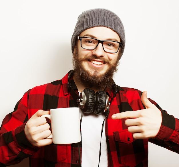 Koncepcja stylu życia, szczęścia i ludzi: młody brodaty mężczyzna z filiżanką kawy w ręku i pokazując okey, na szarym tle.