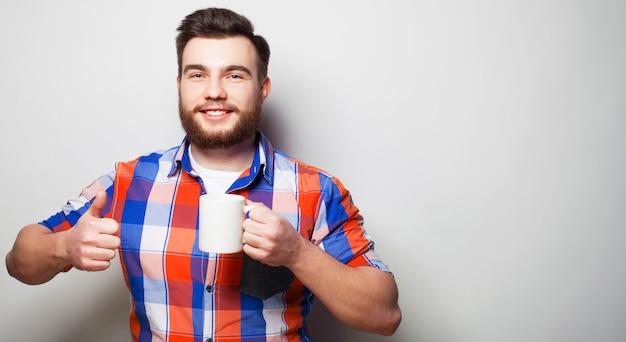 Koncepcja stylu życia, szczęścia i ludzi: młody brodaty mężczyzna z filiżanką kawy w ręku i pokazuje okey, na szarym tle.