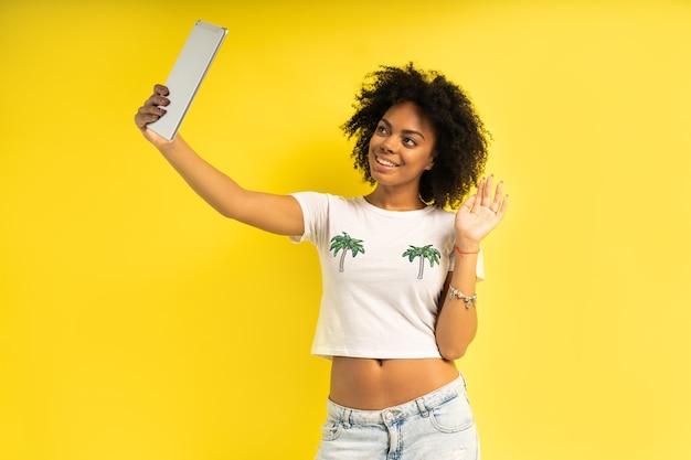 Koncepcja stylu życia - szczęśliwa kobieta za pomocą tabletu do połączeń wideo interakcji na białym tle na żółtym tle