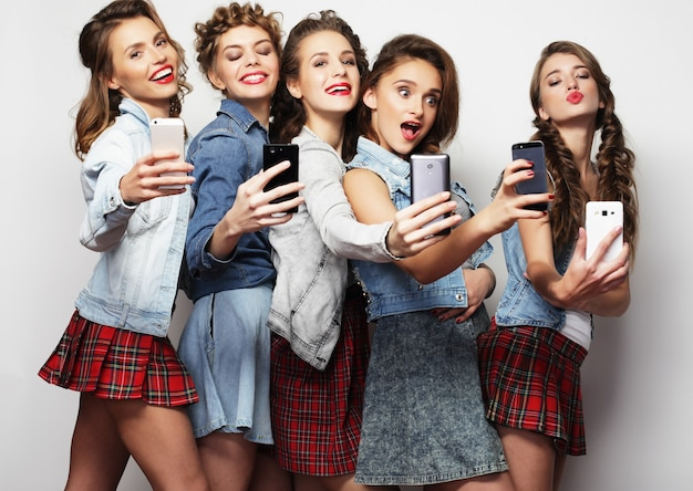 Koncepcja stylu życia, technologii i internetu: grupa młodych kobiet patrzących na swoje smartfony