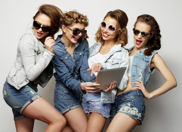 Koncepcja stylu życia, technologii i ludzi: pięć hipsterskich przyjaciółek robi selfie z cyfrowym tabletem