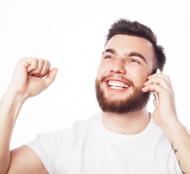 Koncepcja stylu życia, technologii i ludzi: wesoły mężczyzna rozmawiający przez telefon z podniesioną pięścią, otrzymujący dobre wieści.