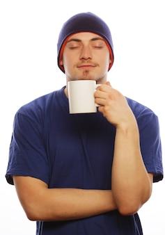 Koncepcja stylu życia, żywności i ludzi: dorywczo młody człowiek trzyma biały kubek z kawą lub herbatą.
