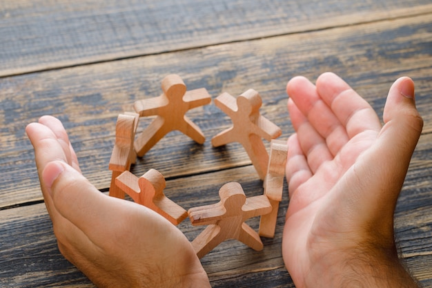 Koncepcja sukcesu firmy na widok z góry drewniany stół. ręce chroniące drewniane figury ludzi.