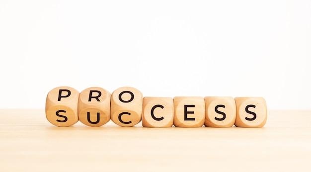 Koncepcja sukcesu procesu. drewniany klocek odwróć proces tekstowy do sukcesu na drewnianym stole. skopiuj miejsce