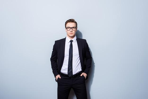 Koncepcja sukcesu. stylowy młody prawnik, stojący na czystej przestrzeni, ubrany w czarny garnitur, krawat, wygląda tak elegancko i kujona!