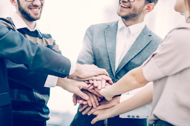 Koncepcja sukcesu w biznesie: przyjazny zespół biznesowy stojący w kręgu i łączący ręce razem