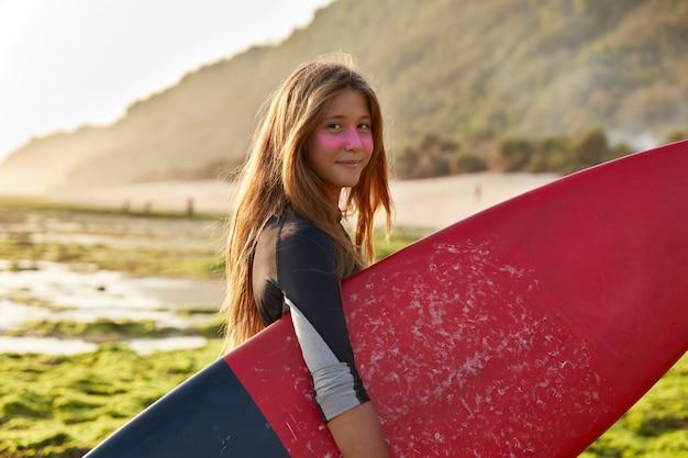 Koncepcja surfer i ocean. zadowolona ciemnowłosa kobieta nosi woskowaną deskę surfingową z zadowolonym wyrazem