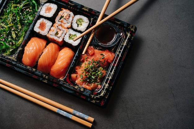 Koncepcja sushi na wynos. pudełko z sushi. z roladkami sushi i pałeczkami. maki. sashimi. łosoś. tuńczyk. wasabi. azjatyckie. język japoński.