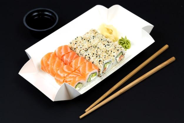 Koncepcja sushi to go, papierowe pudełko na wynos z rolkami sushi