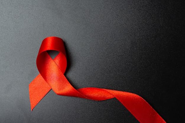 Koncepcja świadomości hiv z czerwoną wstążką światowy dzień walki z aids i światowy dzień zdrowia seksualnego.