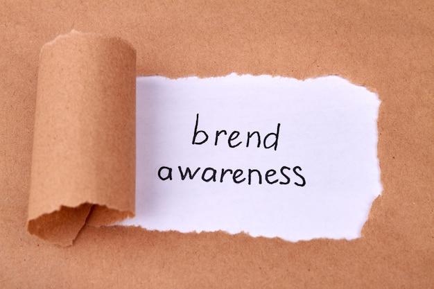 Koncepcja świadomości marki z odkrytym beżowym papierem i ujawnionym przesłaniem