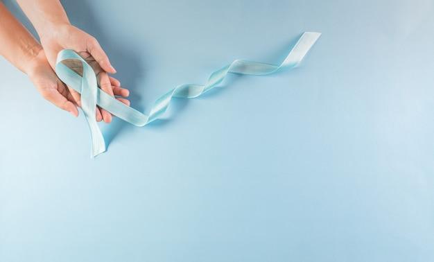 Koncepcja świadomości światowego dnia cukrzycy. ręka trzyma niebieską wstążkę