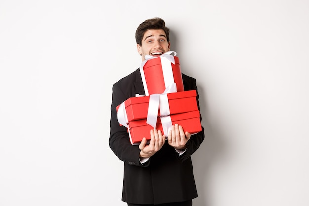Koncepcja świąt bożego narodzenia, uroczystości i stylu życia. obraz szczęśliwego mężczyzny w garniturze niosącego prezenty na nowy rok, trzymającego pudełka z prezentami i uśmiechającego się, stojącego na białym tle