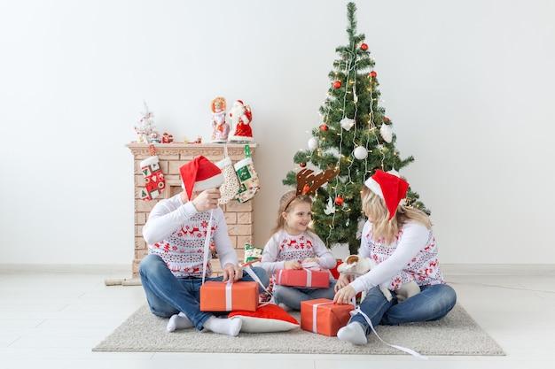 Koncepcja świąt i prezentów - portret szczęśliwej rodziny otwierającej prezenty w czasie świąt bożego narodzenia.