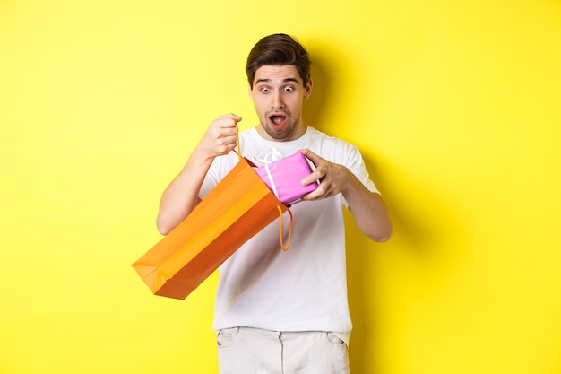 Koncepcja świąt i uroczystości. młody człowiek wyglądający zaskoczony, jak wyjąć prezent z torby na zakupy, stojąc na żółtym tle.