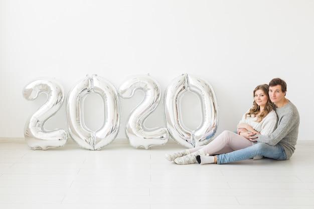 Koncepcja świąt, świąt i imprez - szczęśliwa kochająca para siedzi na podłodze w pobliżu srebrnych balonów 2020. obchody nowego roku
