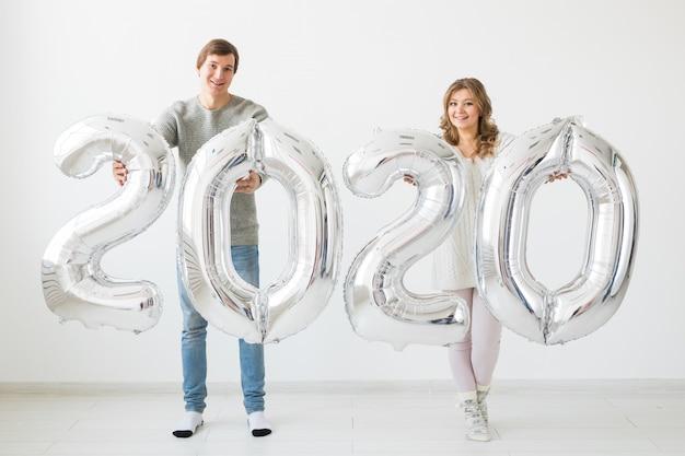 Koncepcja świąt, świąt i imprez - szczęśliwa kochająca para trzyma srebrne balony 2020. obchody nowego roku