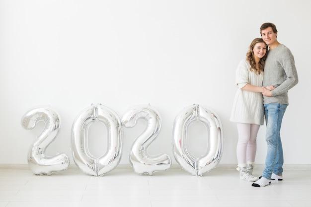 Koncepcja świąt, świąt i imprez - szczęśliwa para kochających w pobliżu srebrnych balonów 2020. obchody nowego roku