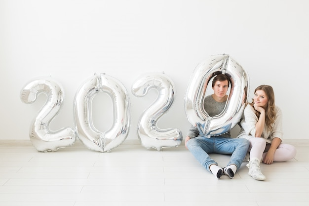 Koncepcja świąt, świąt i imprez - zabawna para siedzi na podłodze w pobliżu srebrnych balonów 2020. obchody nowego roku