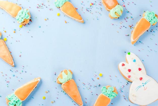 Koncepcja świąt wielkanocnych, słodkie ciasteczka w postaci marchewki, króliczek wielkanocny, ze słodkimi posypkami, jasnoniebieskie tło kopia przestrzeń widok z góry, tło z życzeniami