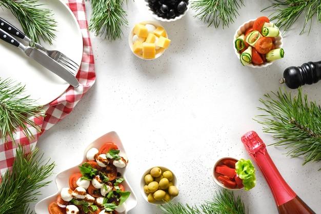 Koncepcja świątecznej kolacji z sałatką caprese i różnymi daniami warzywnymi.