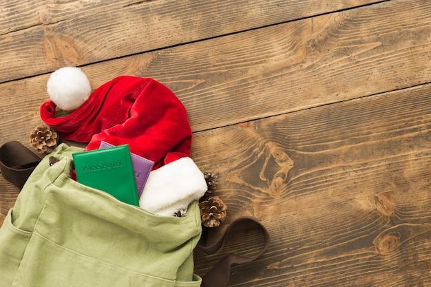Koncepcja świątecznej podróży. plecak z czapką mikołaja i paszporty na drewnianym stole widok z góry
